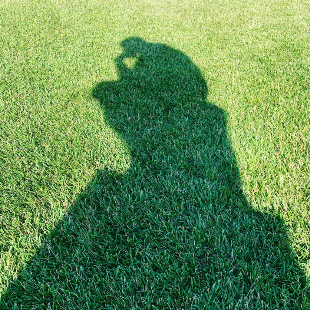 "Shadow on green grass of August Rodin's ""The Thinker"" sculpture at the Nelson-Atkins Museum of Art."
